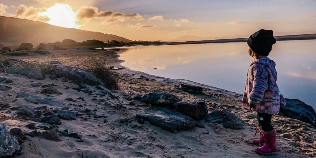 Kind op het strand in Spanje bij zonsopgang
