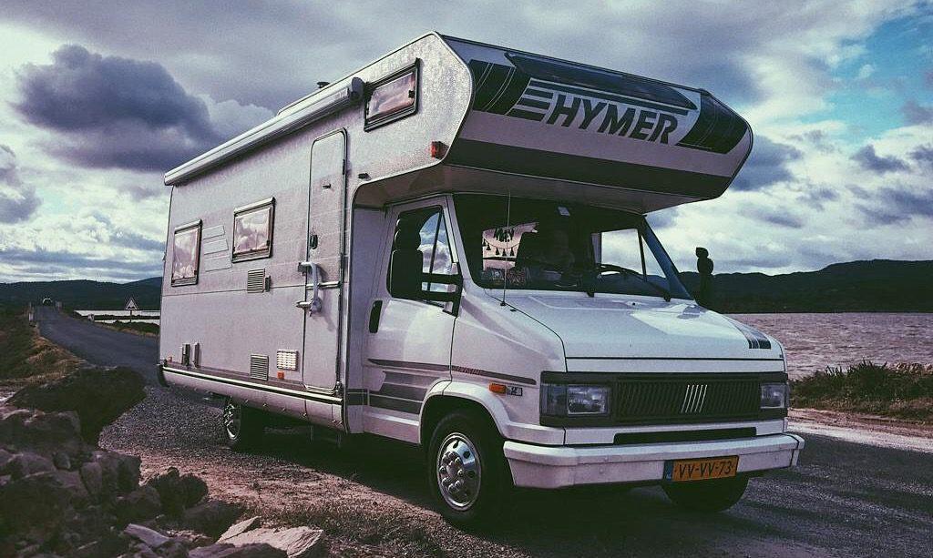 Dit is de camper die wij gingen kopen waarmee we lang op reis konden gaan. Hier zie je onze Hymer camper op een dijk omringd door water in de kleuren grijs wit blauw en paars.