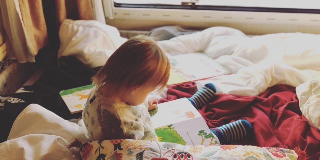 Mickey leest een boekje op bed in onze Hymer camper.