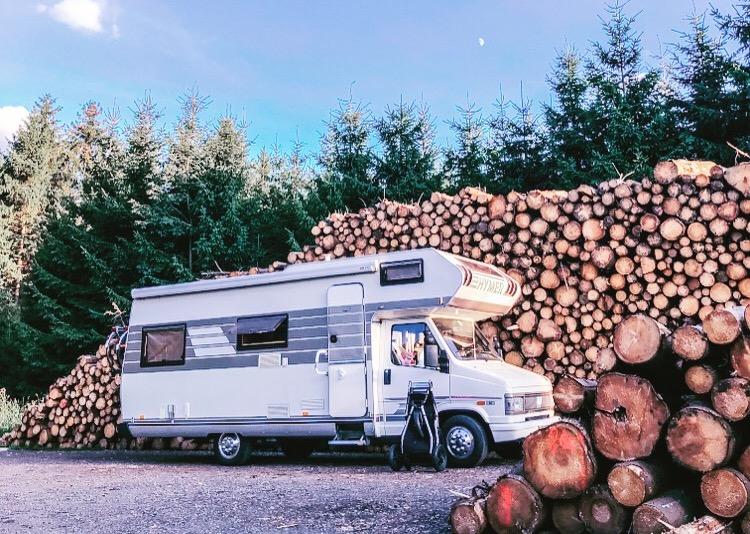 Onze Hymer camper bij een bos, geparkeerd voor een heleboel boomstammen. Toen we bezig waren om een camper te kopen waarmee we lang op reis konden gaan droomden we hier al van.