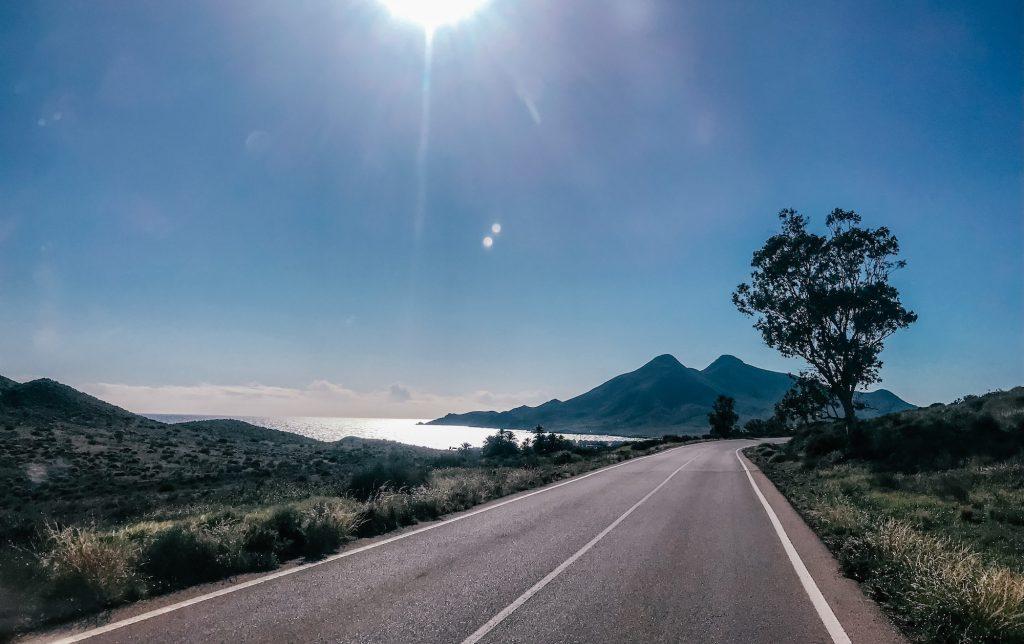 Weg in Spanje met in de verte bergen en de zee, onder een blauwe hemel met een fel stralende zon.