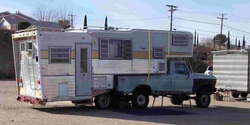Foto van een zelfgebouwde camper op een pickup truck die uit meerdere campers lijkt te bestaan. Ga jij een camper kopen of bouwen waarmee je lang op reis kunt gaan?