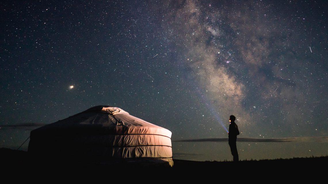 Persoon naast een yurt s'nachts, met de sterrenhemel op de achtergrond