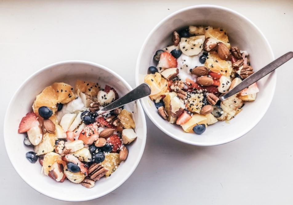 Een gezond ontbijtje: een bakje met plantaardige yoghurt, banaan, aardbeien, sinaasappel, appel, pecannoten, amandelen, chiazaadjes en kokosrasp.