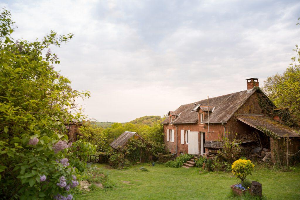 Klein bruin huisje in een grote groene tuin.