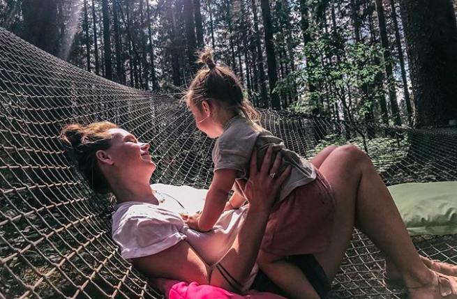 Vera ligt met Mickey in een enorm trampoline net dat opgehangen is tussen de bomen in het bos. Dit was de foto bij het Instagram bericht over hoe moeilijk het is om een huis te kopen en wat ik daarbij voel.
