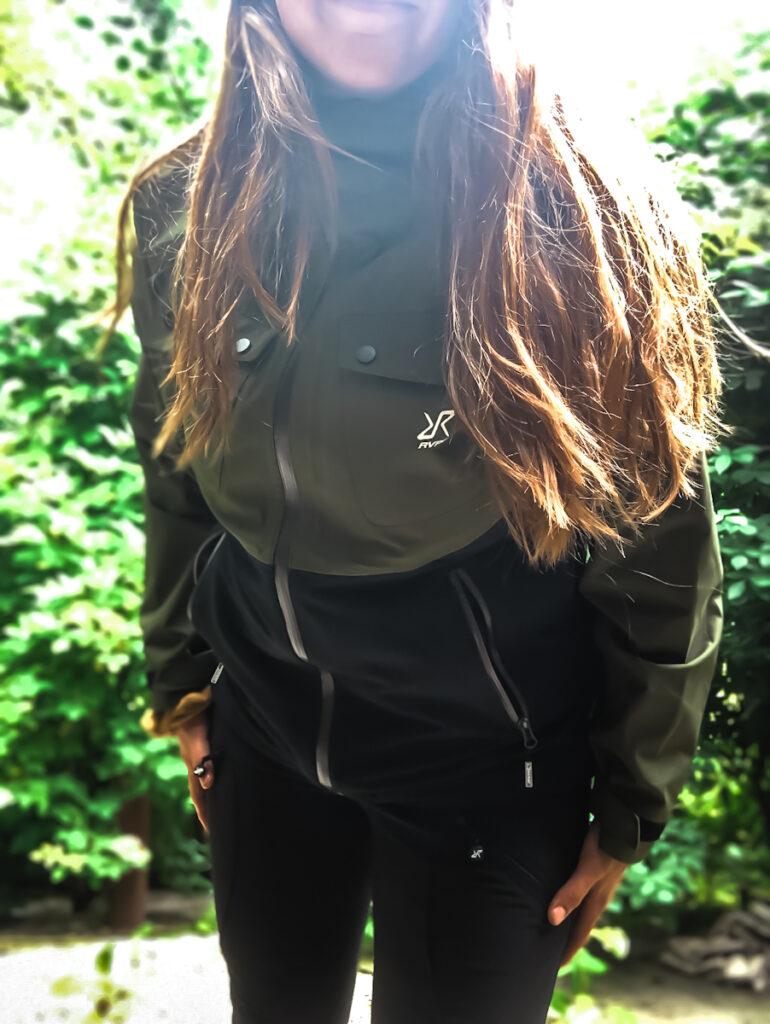 Close up van Vera's groene jas van Revolution Race tegen een achtergrond van groene bladeren