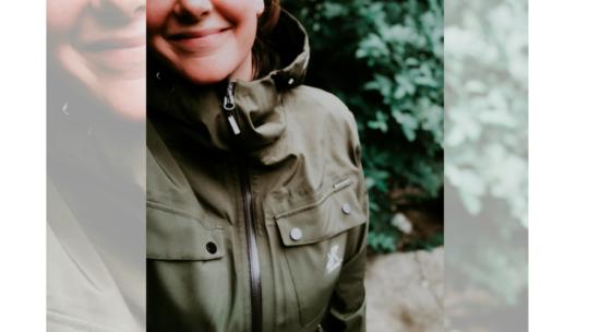 Close up van Vera in een groene jas van Revolution Race tegen een achtergrond van groene bladeren